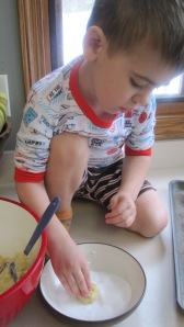 We're getting better about working with dough that has raw egg in it.  He understands now that he shouldn't wipe his doughy hands on his shirt!