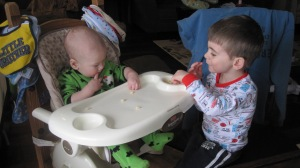 Brothers sharing baby puffs.